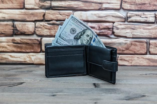 Ein geldbeutel mit rechnungen von hundert dollar auf einem holztisch auf einem wandhintergrund des roten backsteins. Premium Fotos