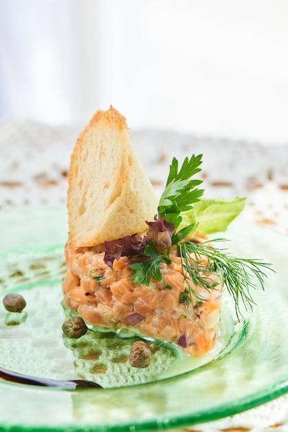 Ein gericht aus lachstatar, roten und grünen zwiebeln, zitronenschale und olivenöl, serviert auf einem teller Premium Fotos