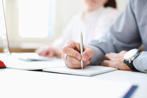 Ein geschäftsmann hält einen stift in der hand. unterschreiben sie. bild mit schärfentiefe. Premium Fotos