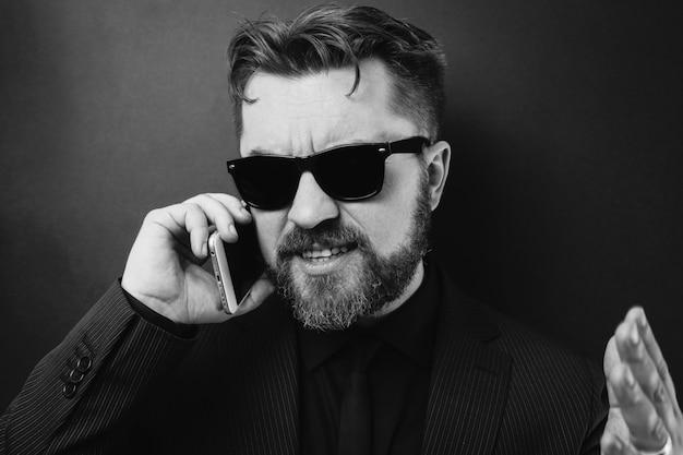 Ein geschäftsmann in einem schwarzen anzug schwört per telefon. Premium Fotos