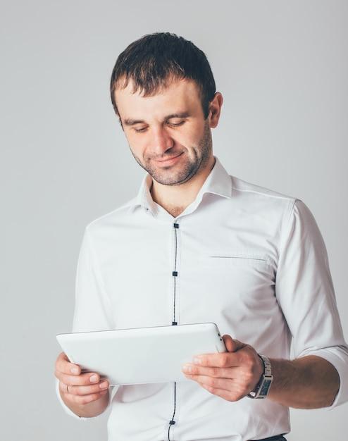 Ein geschäftsmann lächelt und hält eine weiße tablette in seinen händen. ein mann steht in luxuriösem hemd Premium Fotos