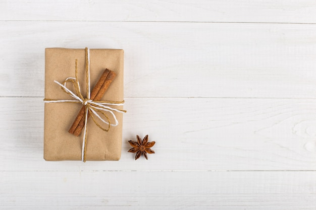 Ein geschenk des kraftpapiers mit zimt- und sternanis auf einer weißen tabelle. Premium Fotos
