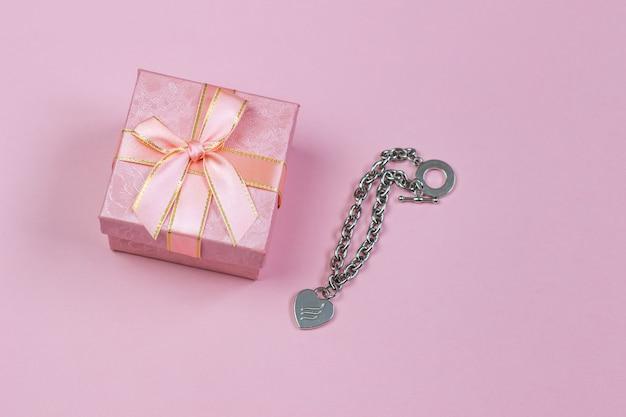 Ein geschenk in einem schönen kasten und in einer halskette mit einem herzen auf einem rosa hintergrund Premium Fotos