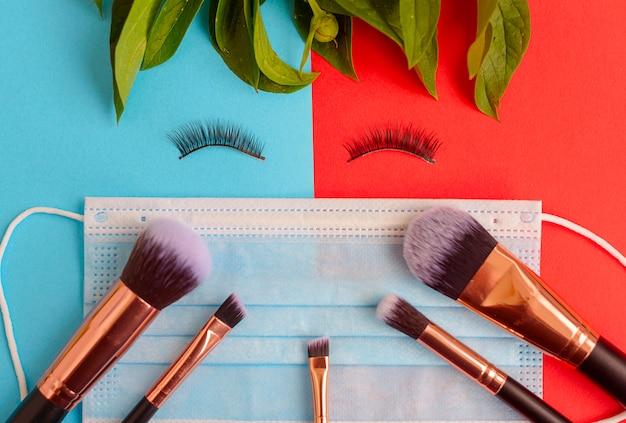 Ein gesicht aus falschen wimpern, eine schützende gesichtsmaske und make-up-pinsel auf einem farbigen roten und blauen hintergrund, eine kreative wohnung lag während einer pandemie Premium Fotos