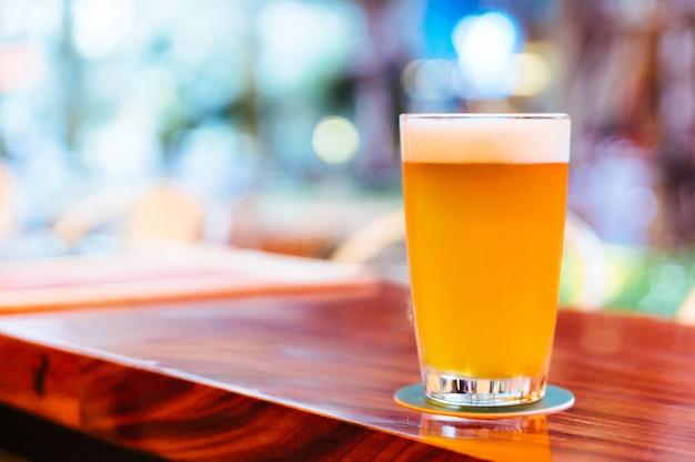 Ein glas bier vom fass mit schaum auf hölzernem zähler mit unschärfe und bokeh hintergrund. Premium Fotos