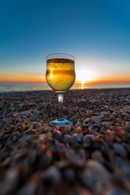 Ein glas champagner an der küste steht auf dem sand gegen den sonnenuntergang Premium Fotos