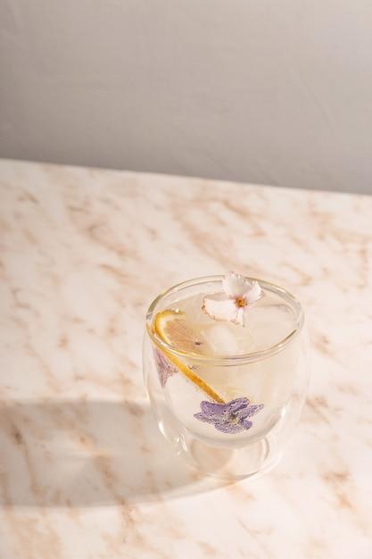 Ein glas eiswasser mit blumen auf marmortisch verziert Premium Fotos