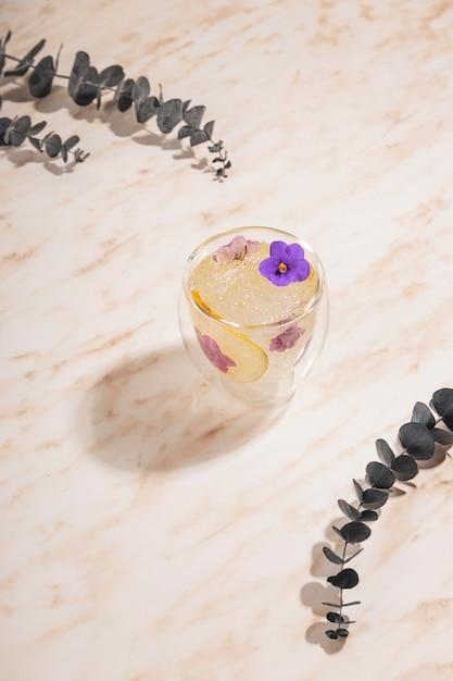 Ein glas eiswasser mit blumen mit eukalyptuszweigen auf einem marmortisch. Premium Fotos