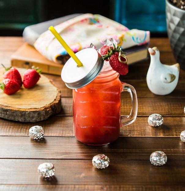 Ein glas erdbeeresmoothie mit eiswürfeln. Kostenlose Fotos