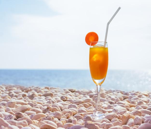Ein glas frischer orangensaft mit eis und karottenscheibe am weißen kieselstrand Premium Fotos
