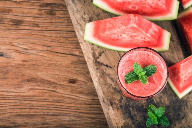 Ein glas frischer wassermelonensaft auf einem hintergrund des hölzernen brettes Premium Fotos