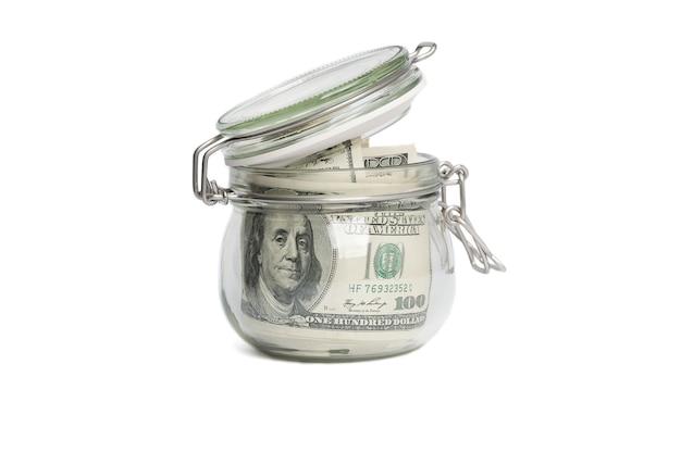 Ein glas gefüllt mit dollar unter hundert dollarscheinen. Premium Fotos
