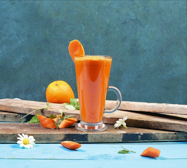 Ein glas grapefruit-smoothie auf einem stück holz. Kostenlose Fotos