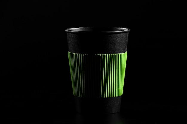 Ein glas heißen tee oder kaffee. schwarzes papierglas mit einem deckel auf einem schwarzen hintergrund. Premium Fotos