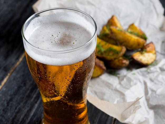Ein glas helles bier mit einem snack in form von rustikalen kartoffeln mit dill auf einem dunklen hölzernen hintergrund Premium Fotos
