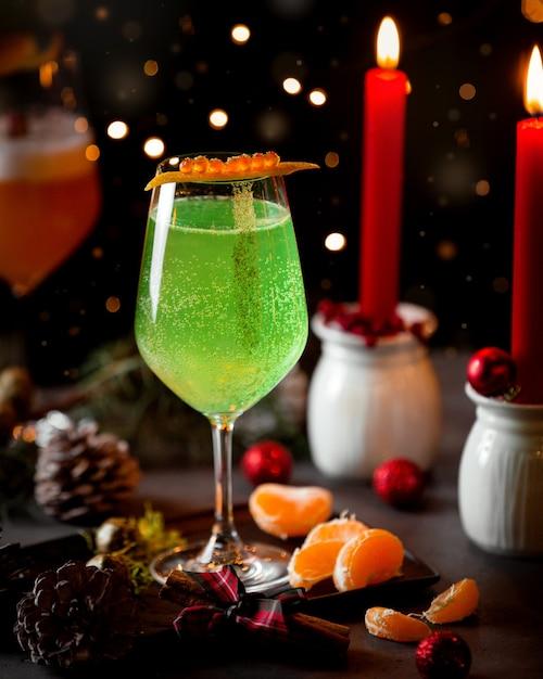 Ein glas kohlensäurehaltiges grünes getränk und mandarine Kostenlose Fotos