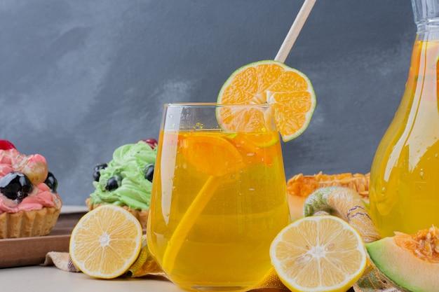 Ein glas limonade und cremige cupcakes auf dem tisch. Kostenlose Fotos
