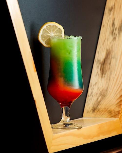 Ein Glas Ombre-cocktail In Den Farben Grün Und Orange Mit