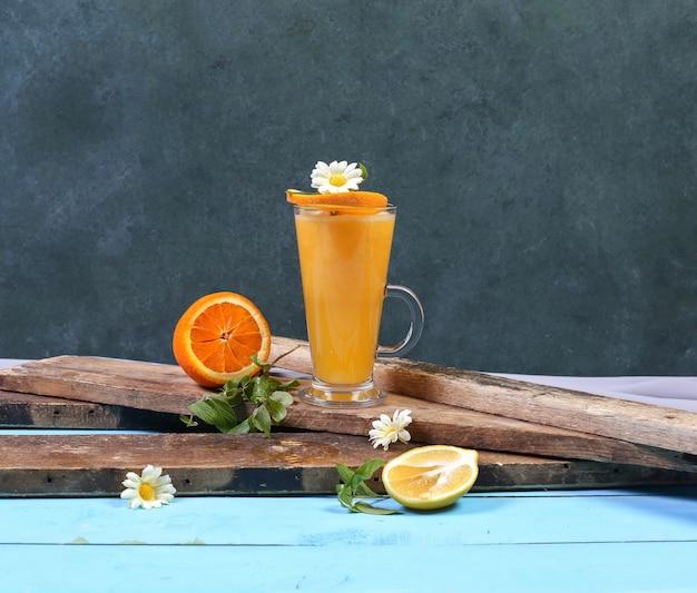 Ein glas orange smoothie auf einem stück holz. Kostenlose Fotos