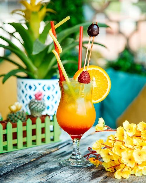 Ein glas orangensaft, garniert mit erdbeere, orangenscheibe und kirsche Kostenlose Fotos