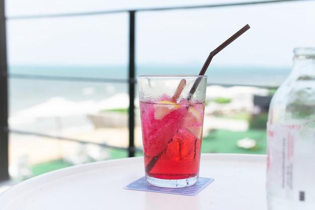 Ein glas wasser mit rotem getränk auf weißer tabelle Premium Fotos