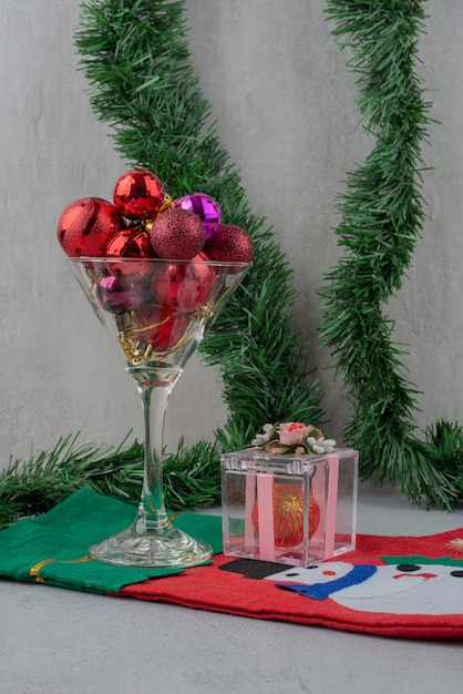 Ein glas weihnachtskugeln mit socke an grauer wand. Kostenlose Fotos