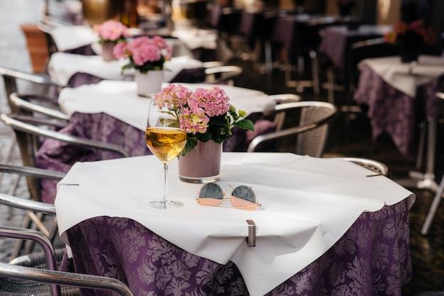 Ein glas wein auf dem tisch eines schönen coffeeshops mitten in europa. sich ausruhen Premium Fotos