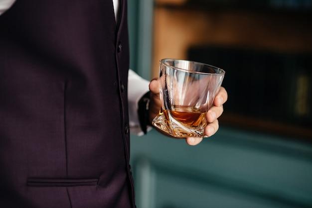 Ein glas weinbrand in männlicher hand Premium Fotos