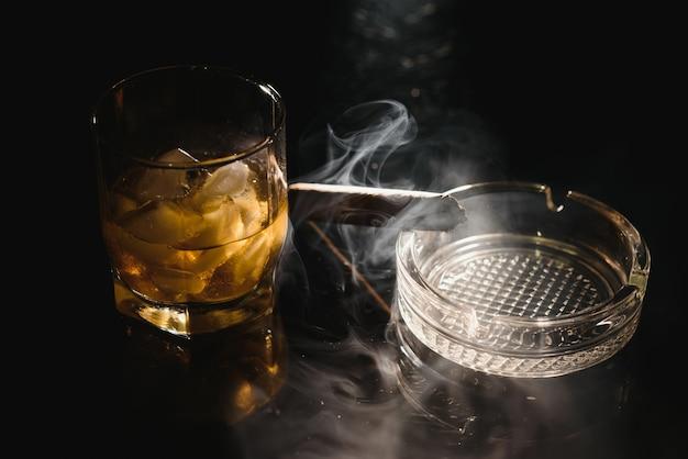 Ein glas whisky oder bourbon mit eiswürfeln und eine zigarre auf einer schwarzen tafel mit rauch Premium Fotos