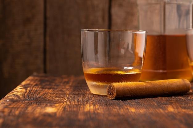 Ein glas whisky und zigarre auf holztisch hautnah Premium Fotos