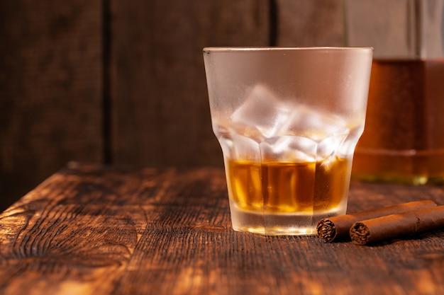 Ein glas whisky und zigarre auf holztisch Premium Fotos