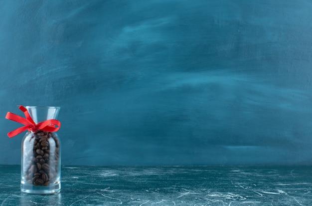 Ein glaskrug voller kaffeebohnen auf einem blauen hintergrund. hochwertiges foto Kostenlose Fotos