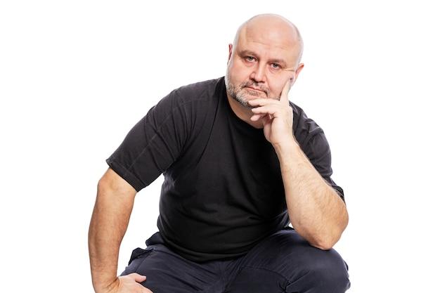 Ein glatzköpfiger mann mittleren alters in einem schwarzen t-shirt sitzt mit der hand im gesicht. isoliert weiß Premium Fotos