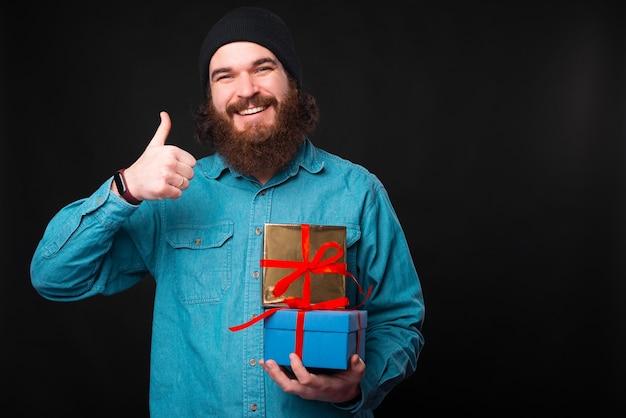 Ein glücklicher bärtiger mann lächelt in die kamera und hält einen daumen hoch und einige geschenke zeigen, dass er die geschenke mag Premium Fotos