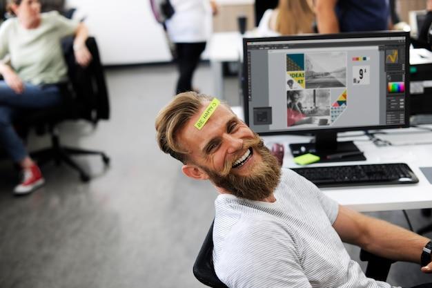 Ein glücklicher bartmann im büro Kostenlose Fotos