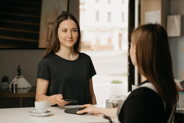 Ein glückliches mädchen mit langen haaren, das ihren kaffee mit einem smartphone durch kontaktlose nfc-technologie in einem café bezahlt. eine brünette barista-frau hält einem kunden ein terminal zum bezahlen hin. Premium Fotos
