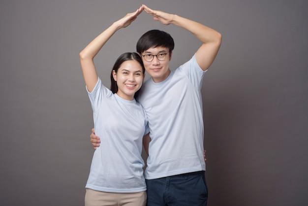 Ein glückliches paar, das blaues hemd trägt, macht armdach in grau Premium Fotos