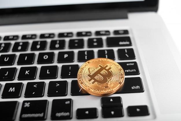 Ein goldenes bitcoin als welthaupt-kryptowährung, platziert auf laptoptastatur. Premium Fotos