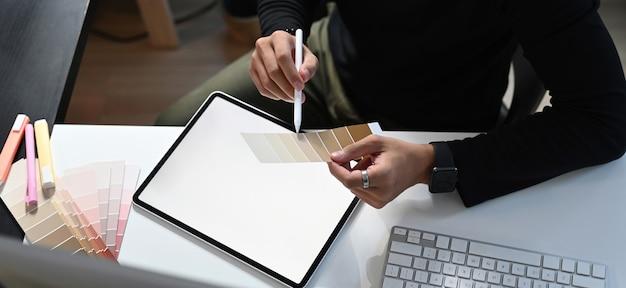 Ein grafikdesigner arbeitet am arbeitsplatz an der farbauswahl und dem digitalen tablet. Premium Fotos