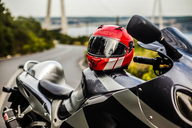 Ein grau-schwarzes motorrad und ein roter helm. Kostenlose Fotos