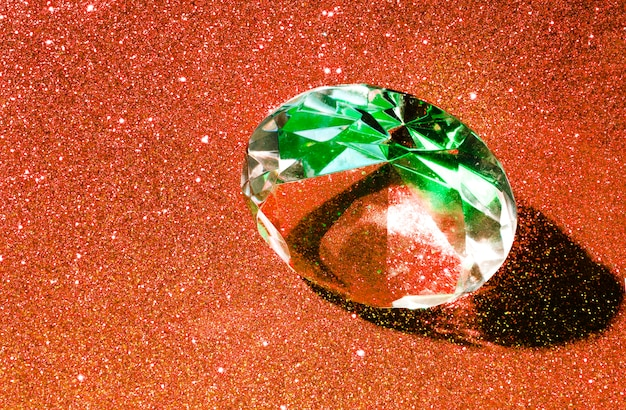 Ein großer kristalldiamant auf einem orange glänzenden hellen hintergrund Kostenlose Fotos