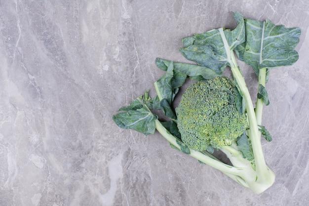 Ein grüner brokkoli isoliert auf einer marmoroberfläche Kostenlose Fotos