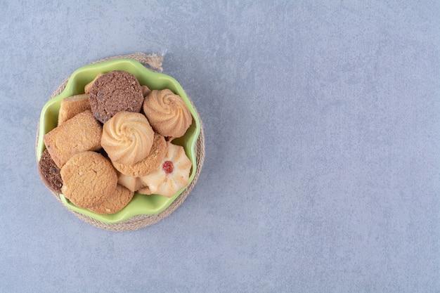 Ein grüner teller mit süßen runden leckeren keksen auf sackleinen. Kostenlose Fotos