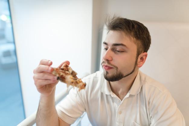 Ein gutaussehender mann schaut sich ein stück pizza in seinen händen genau an. der student isst pizza zum mittagessen. Premium Fotos