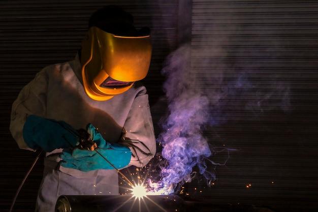 Ein handwerker schweißt mit werkstückstahl.arbeiter über schweißerstahl elektroschweißgerät verwenden in der fabrikindustrie treten lichtlinien und sicherheitsausrüstung aus. Premium Fotos