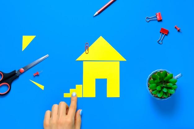 Ein haus aus farbigem papier ausgeschnitten. die finger der frau befestigen die treppe. das konzept, den traum vom eigenen zuhause zu verwirklichen, gehäuse zu kaufen und zu bauen. Premium Fotos