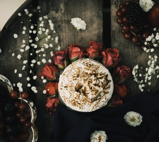 Ein heißer kaffee der oberen nahaufnahme, der auf den roten rosen und der braunen rustikalen holzoberfläche lecker schmeckt Kostenlose Fotos