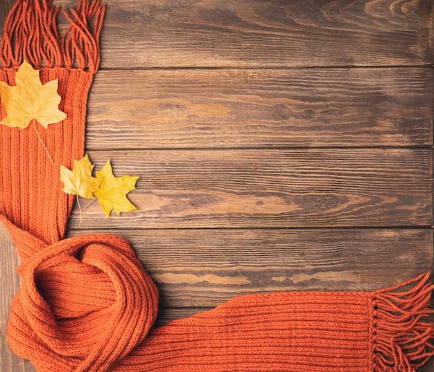 Ein heller gestrickter orange gestrickter schal und ein ahornblatt liegt auf einem hölzernen hintergrund. flaches layout. Premium Fotos