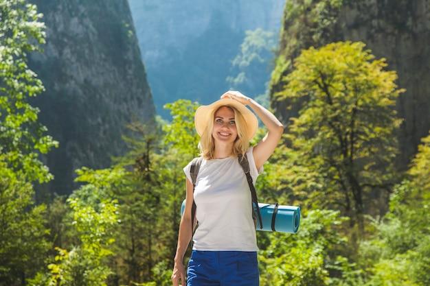 Ein hipster-mädchen mit hut reist in die berge das mädchen liebt es zu reisen. ansicht von der rückseite des touristischen reisenden auf hintergrundberg Premium Fotos