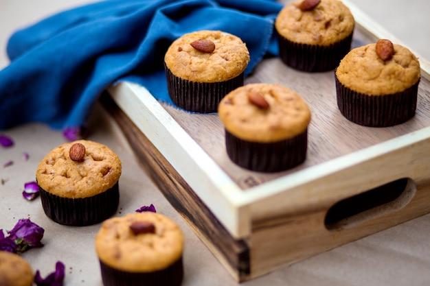 Ein hölzernes tablett mit einfachen muffins mit mandeln an der spitze Kostenlose Fotos